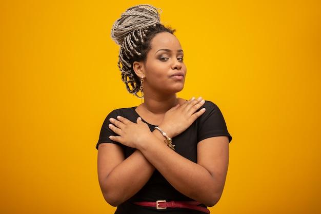 Belle jeune femme afro-américaine aux cheveux de la peur sur jaune Photo Premium