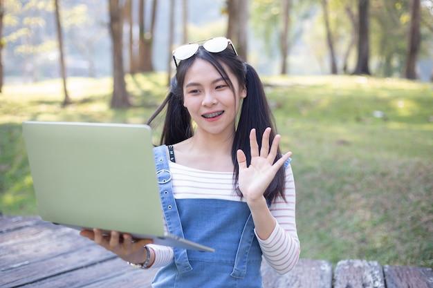 Belle jeune femme à l'aide d'un ordinateur portable Photo gratuit