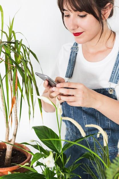 Belle jeune femme à l'aide de téléphone portable près de plantes en pot Photo gratuit