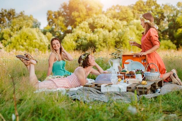Belle jeune femme amie filles femmes sur un pique-nique en été amusant pour célébrer et boire du vin. Photo Premium