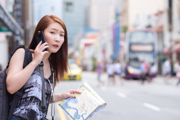 Belle jeune femme appelant un taxi public par téléphone en ville Photo Premium