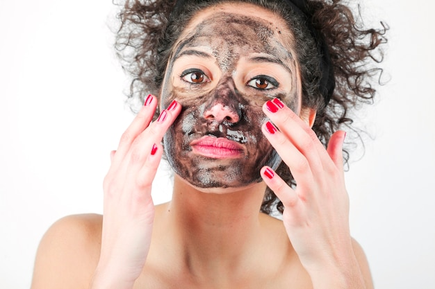 Belle jeune femme appliquant un masque noir avec ses doigts sur fond blanc Photo gratuit