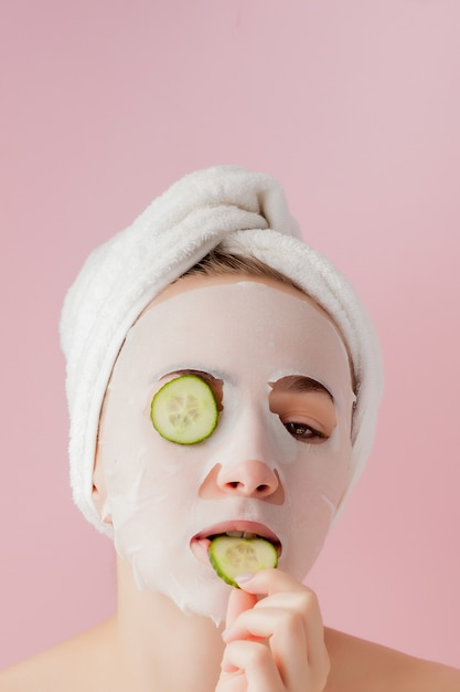 Belle jeune femme applique un masque de tissu cosmétique sur un visage avec du concombre Photo Premium