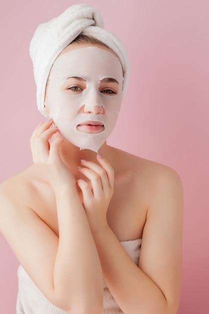 Belle Jeune Femme Applique Un Masque De Tissu Cosmétique Sur Un Visage Sur Un Espace Rose Photo Premium