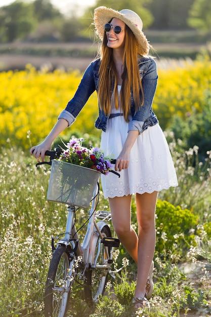 Belle jeune femme appréciant le printemps dans un champ. Photo gratuit