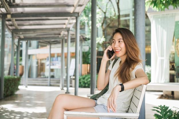 Belle jeune femme asiatique à l'aide de smartphone pour parler Photo gratuit