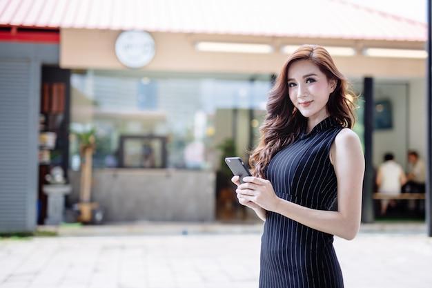 Belle jeune femme asiatique à l'aide de smartphone. Photo Premium