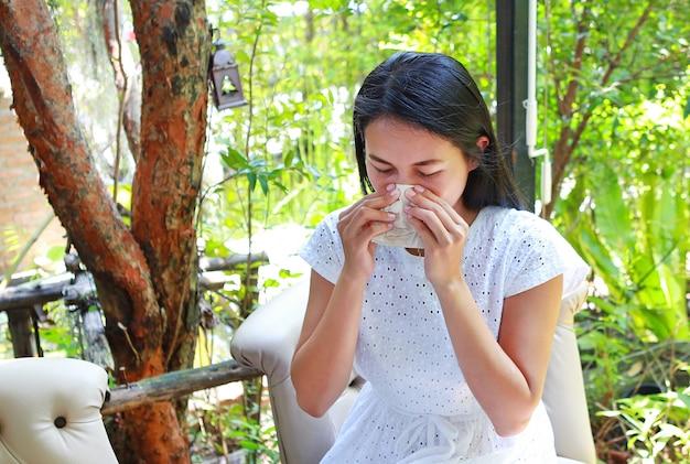 Belle jeune femme asiatique assise au café à l'aide d'un mouchoir Photo Premium