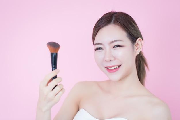 Belle jeune femme asiatique caucasienne sourire appliquant le maquillage naturel poudre cosmétique brosse. cosmétologie, soin de la peau, nettoyage du visage Photo Premium