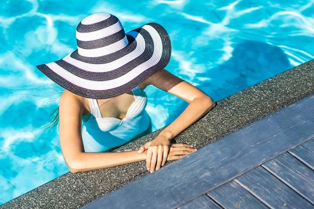 Belle jeune femme asiatique avec un chapeau dans la piscine pour les voyages et les vacances Photo gratuit