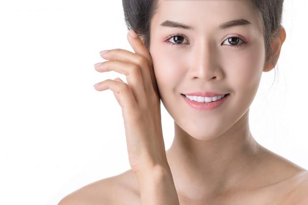 Belle jeune femme asiatique avec des cosmétiques sur son propre visage Photo Premium