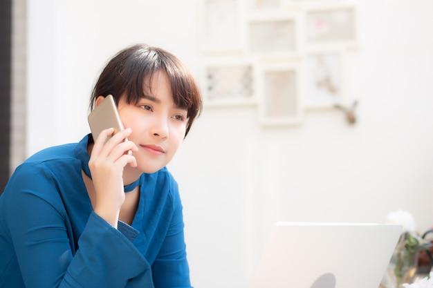 Belle jeune femme asiatique excitée et heureuse du travail avec ordinateur portable Photo Premium