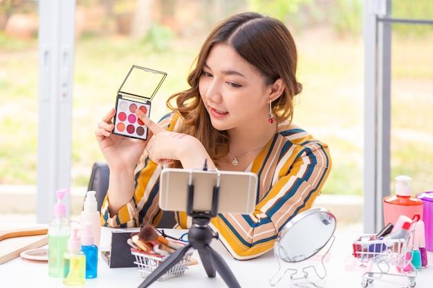 Belle Jeune Femme Asiatique Faisant L'examen Du Produit En Ligne à La Maison Photo Premium