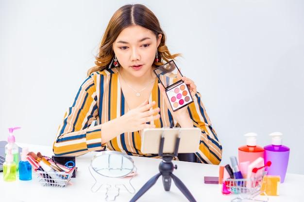 Belle Jeune Femme Asiatique Faisant L'examen Des Produits En Ligne à La Maison Photo Premium