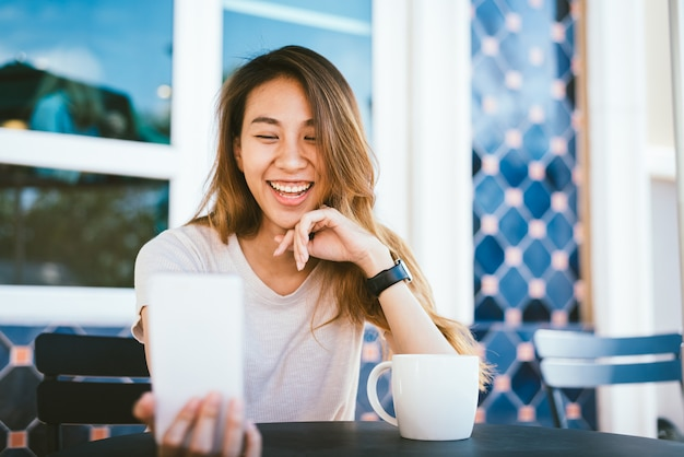 Belle jeune femme asiatique heureuse prenant un selfie à l'aide d'un téléphone intelligent au café Photo gratuit