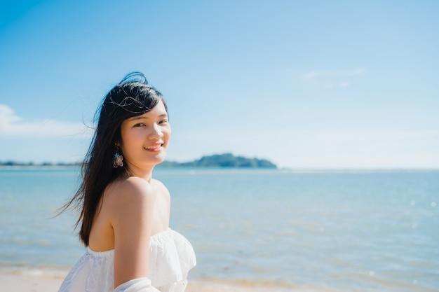 Belle jeune femme asiatique heureuse se détendre à pied sur la plage près de la mer. Photo gratuit