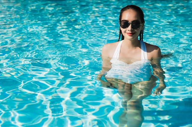 Belle jeune femme asiatique heureuse et souriante dans la piscine pour se détendre et voyager Photo gratuit