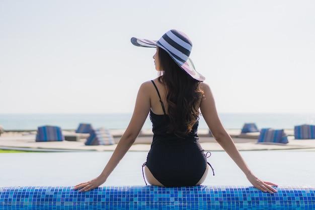 Belle jeune femme asiatique heureuse sourire et se détendre dans la piscine Photo gratuit