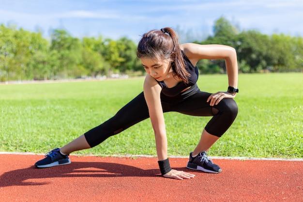 Belle jeune femme asiatique qui s'étend avant d'exercer le matin sur une piste de course à pied Photo Premium