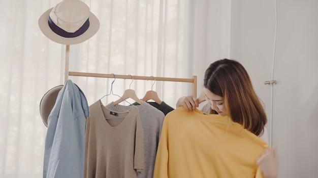 Belle jeune femme asiatique séduisante choisissant ses vêtements de costume de mode dans le placard à la maison Photo gratuit