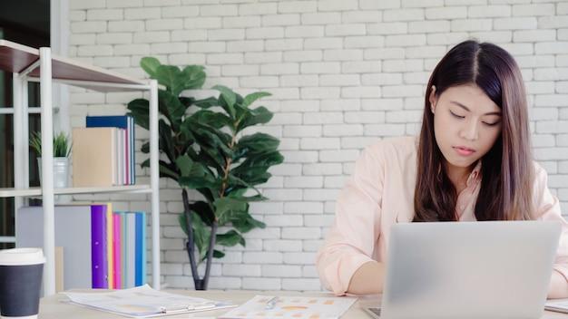 Belle jeune femme asiatique souriante travaillant sur ordinateur portable sur le bureau dans le salon à la maison. Photo gratuit
