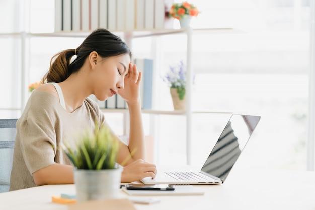 Belle jeune femme asiatique souriante travaillant sur un ordinateur portable sur le bureau dans le salon à la maison Photo gratuit