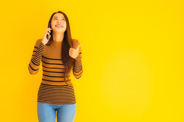 Belle Jeune Femme Asiatique Utilise Un Téléphone Mobile Intelligent Ou Un Téléphone Portable Avec De Nombreuses Actions Sur Le Mur Jaune Photo gratuit