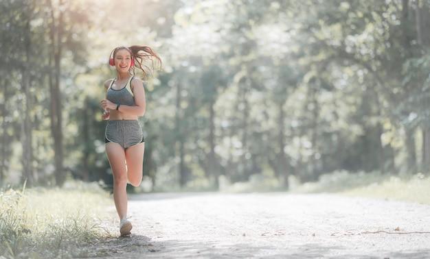 Belle Jeune Femme Asiatique En Vêtements De Sport Et Casque En Plein Air Dans Le Parc Avec Bonheur. Photo Premium
