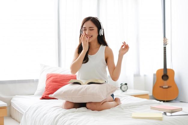 Belle Jeune Femme Asie Relaxante écouter De La Musique Avec Des écouteurs Sur Le Lit à La Maison Photo Premium