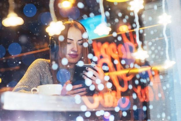 Belle jeune femme assise au café, buvant du café. modèle écoutant de la musique. Photo Premium