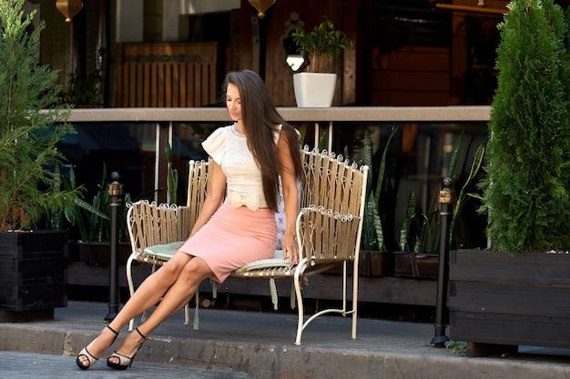 Belle jeune femme assise sur un banc en métal près de la terrasse du café Photo Premium