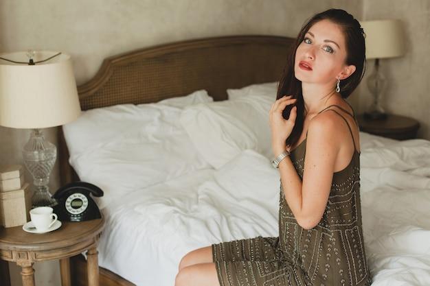 Belle Jeune Femme Assise Sur Le Lit Dans La Chambre D'hôtel, Robe De Soirée élégante, Sexy, Sexy, Tenue De Mode, Draps Blancs Photo gratuit