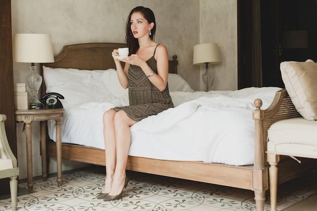 Belle Jeune Femme Assise Sur Le Lit à L'hôtel, Robe élégante, Humeur Sensuelle, Boire Du Café, Tenant La Tasse Photo gratuit