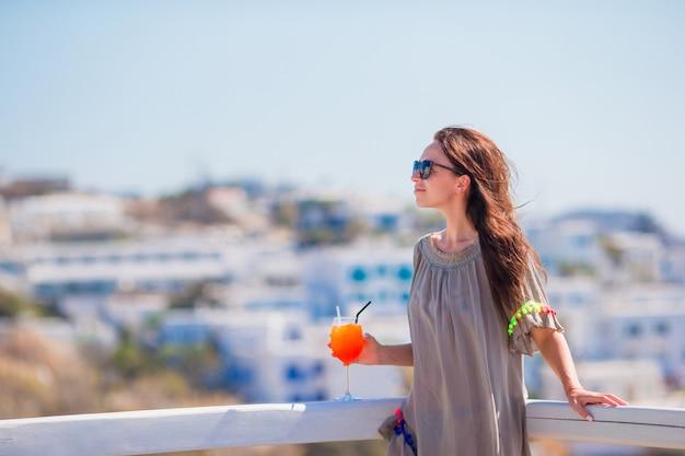 Belle jeune femme au café en plein air avec un cocktail savoureux. happy tourist profiter de vacances européennes avec vue imprenable sur la vieille ville de grèce Photo Premium