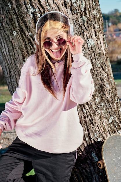 Belle Jeune Femme Au Casque, écouter De La Musique Debout Sur Un Arbre Dans Un Pull Rose Et Avec De Grandes Lunettes De Soleil. Photo Premium