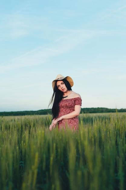 Belle jeune femme au coucher du soleil sur le terrain Photo Premium