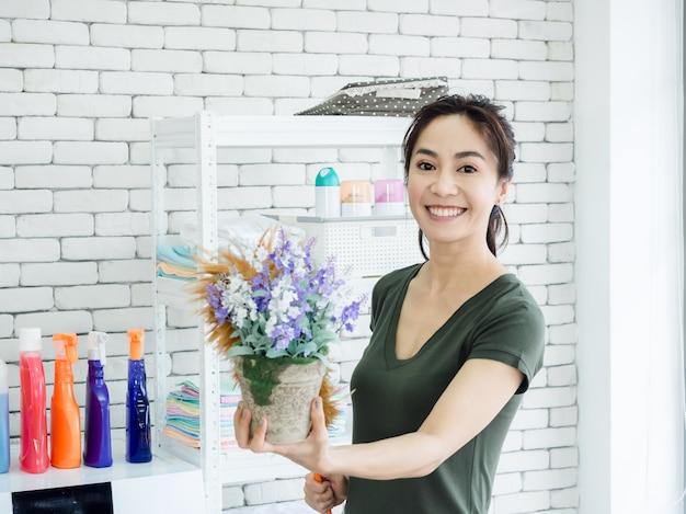 Belle Jeune Femme Au Foyer Femme Asiatique Souriante à L'aide D'un Plumeau De Poulet Pour épousseter Sur Le Vase à Fleurs Dans La Buanderie. Photo Premium
