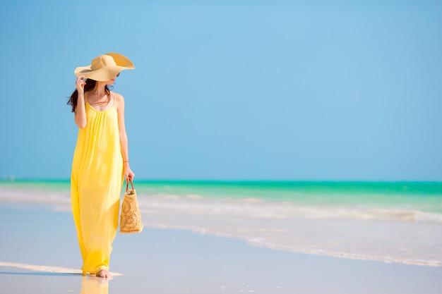 Belle jeune femme au grand chapeau pendant les vacances à la plage tropicale Photo Premium