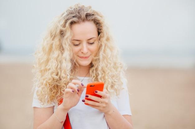Belle Jeune Femme Aux Cheveux Bouclés Et Touffus, Une Peau Propre Et Saine, Détient Un Smartphone Moderne Photo Premium