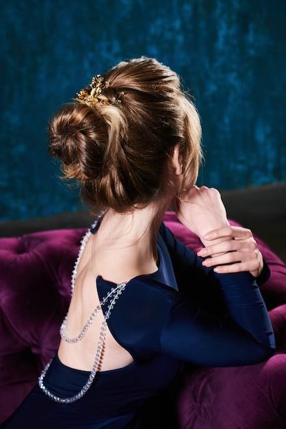 Belle jeune femme aux cheveux clairs se pencha à l'arrière du canapé Photo Premium