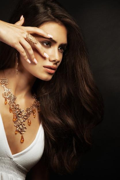 Belle jeune femme aux cheveux longs et aux bijoux. Photo Premium