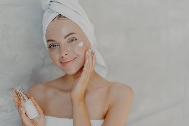 Belle Jeune Femme Aux Yeux Bleus Avec Un Maquillage Naturel Applique La Crème Pour Le Visage Photo Premium