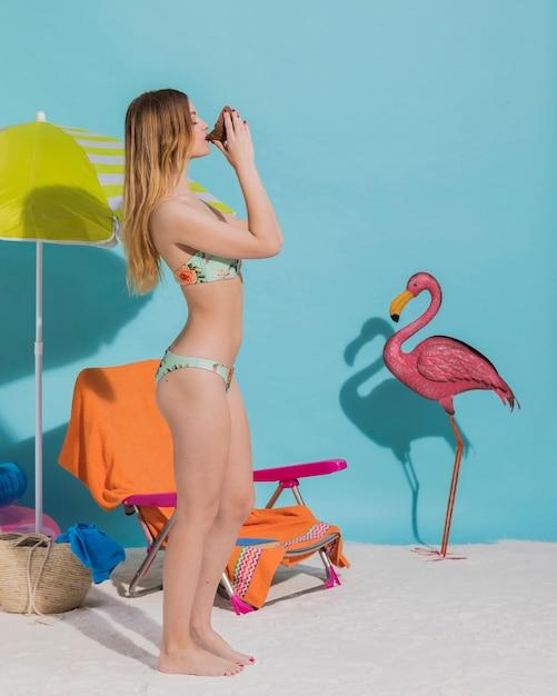 Belle jeune femme en bikini, buvant des boissons en studio Photo gratuit