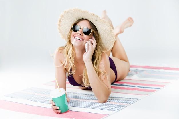 Belle Jeune Femme En Bikini Utilisant Son Téléphone Portable. Isolé Sur Blanc. Photo gratuit