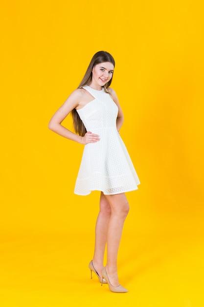Belle jeune femme blonde en belle robe de printemps, posant sur fond jaune en studio Photo Premium
