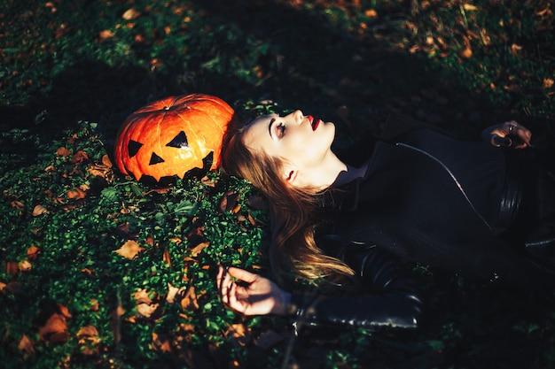Belle jeune femme blonde avec un maquillage extravagant dans une veste en cuir noir Photo Premium