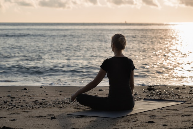 Belle jeune femme blonde en noir faisant du yoga Photo Premium