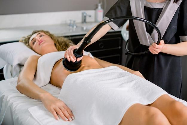 Belle Jeune Femme Blonde Recevant Une Thérapie Anti-cellulite Et Anti-graisse Sur Son Abdomen Dans Un Salon De Beauté. Photo Premium