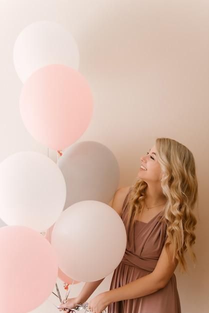 Belle Jeune Femme Blonde Souriante Avec Des Ballons Blancs Gris Et Roses Sur Un Mur Léger Photo Premium