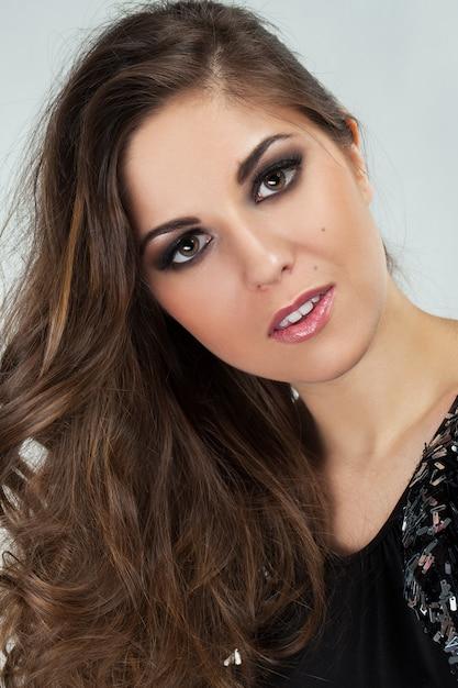 Belle jeune femme avec des boucles et du maquillage Photo gratuit